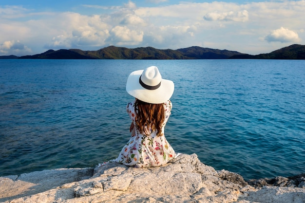 Jonge vrouw zittend op de top van een rots en kijken naar de kust.