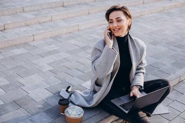 Jonge vrouw zittend op de trap en werkt op de computer