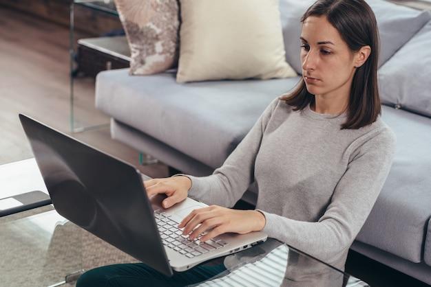 Jonge vrouw zittend op de vloer bij de bank met behulp van laptop.