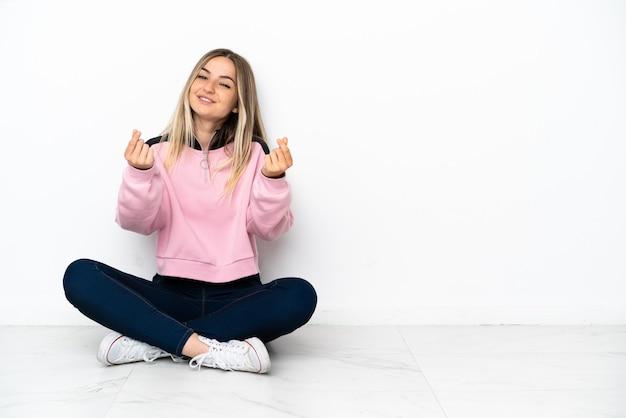 Jonge vrouw zittend op de vloer binnenshuis geld gebaar maken