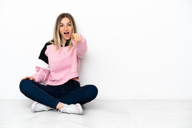 Jonge vrouw zittend op de vloer binnenshuis verrast en naar voren wijzend