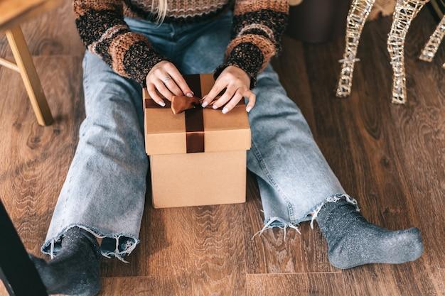 Jonge vrouw zittend op de vloer en een strik op een kerstcadeau binden.