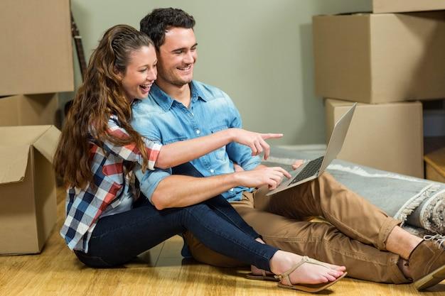 Jonge vrouw zittend op de vloer en met behulp van laptop in hun nieuwe huis