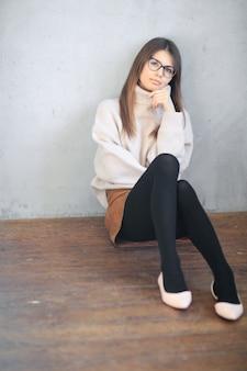 Jonge vrouw zittend op de vloer en poseren