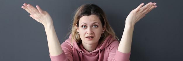 Jonge vrouw zittend op de vloer en spreidt haar armen familie misverstand concept