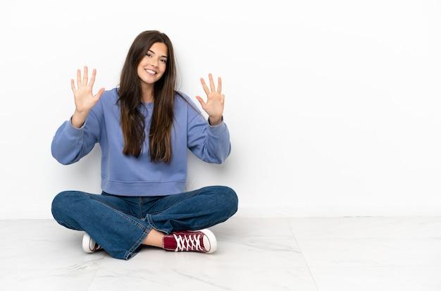 Jonge vrouw zittend op de vloer en telt negen met vingers