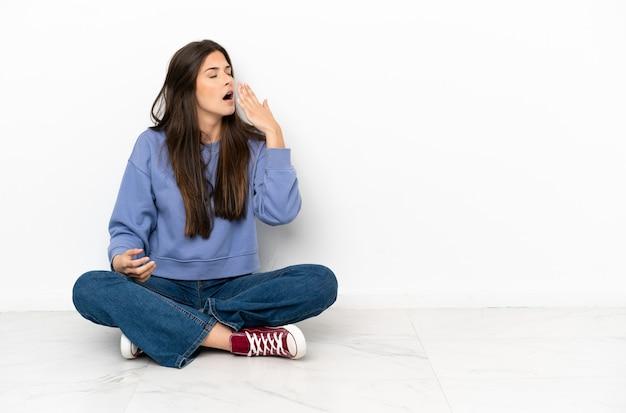 Jonge vrouw zittend op de vloer geeuwen en wijd open mond bedekken met de hand