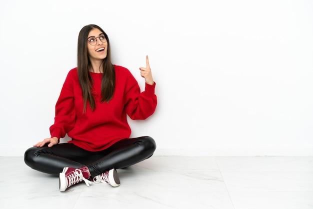 Jonge vrouw zittend op de vloer geïsoleerd op een witte achtergrond die omhoog wijst en verrast