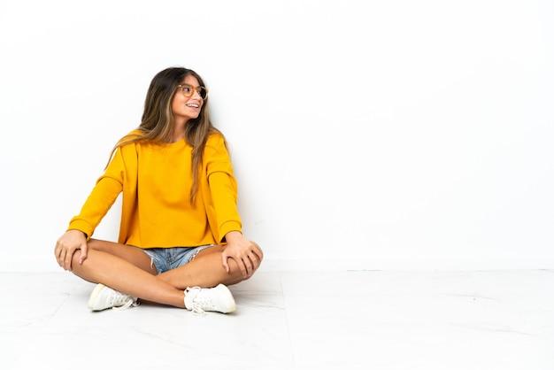 Jonge vrouw zittend op de vloer geïsoleerd op een witte achtergrond in laterale positie