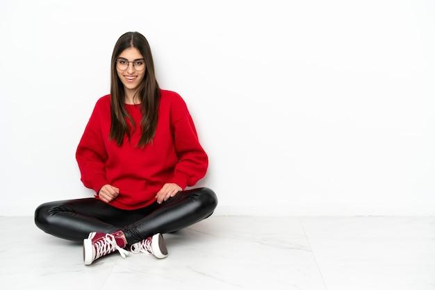Jonge vrouw zittend op de vloer geïsoleerd op een witte achtergrond lachen