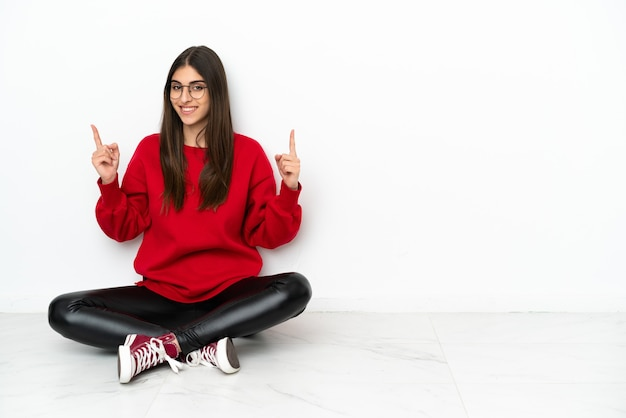 Jonge vrouw zittend op de vloer geïsoleerd op een witte achtergrond met een geweldig idee
