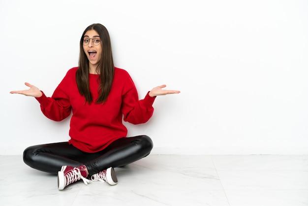 Jonge vrouw zittend op de vloer geïsoleerd op een witte achtergrond met geschokte gezichtsuitdrukking