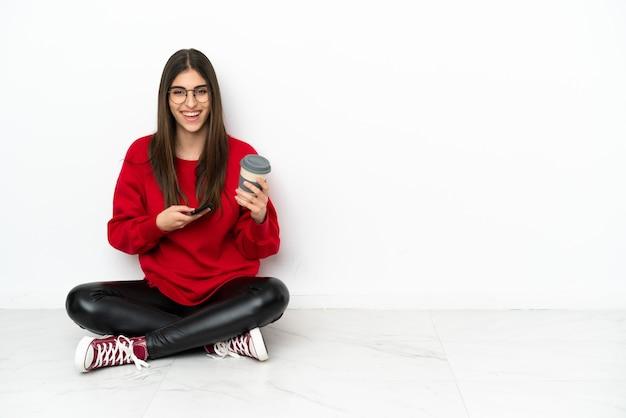 Jonge vrouw zittend op de vloer geïsoleerd op een witte achtergrond met koffie om mee te nemen en een mobiel