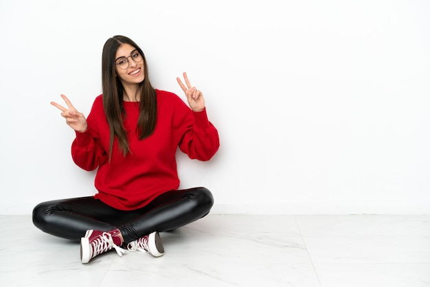 Jonge vrouw zittend op de vloer geïsoleerd op een witte achtergrond met overwinningsteken met beide handen