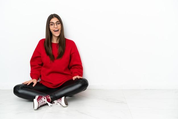 Jonge vrouw zittend op de vloer geïsoleerd op een witte achtergrond met verrassing gezichtsuitdrukking Premium Foto