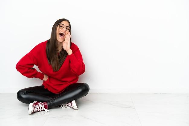 Jonge vrouw zittend op de vloer geïsoleerd op een witte achtergrond schreeuwen met wijd open mond