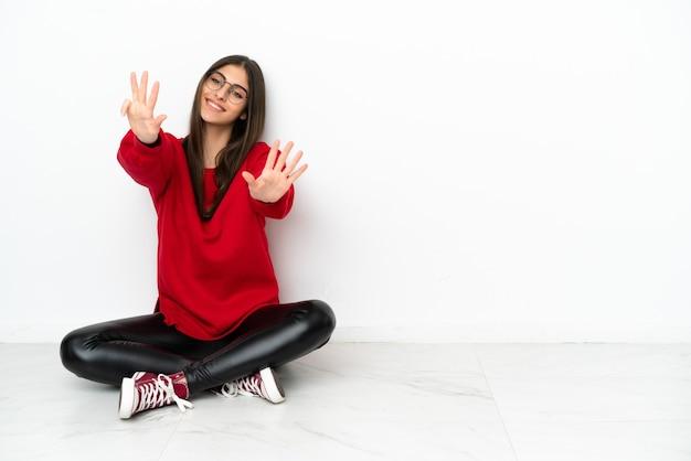 Jonge vrouw zittend op de vloer geïsoleerd op een witte achtergrond telt negen met vingers