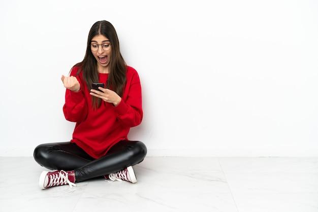 Jonge vrouw zittend op de vloer geïsoleerd op een witte achtergrond verrast en het verzenden van een bericht