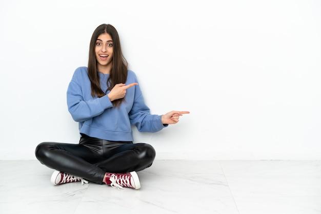Jonge vrouw zittend op de vloer geïsoleerd op een witte achtergrond verrast en wijzende kant