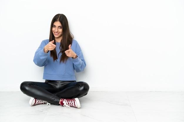 Jonge vrouw zittend op de vloer geïsoleerd op een witte achtergrond wijst vinger naar je met een zelfverzekerde uitdrukking