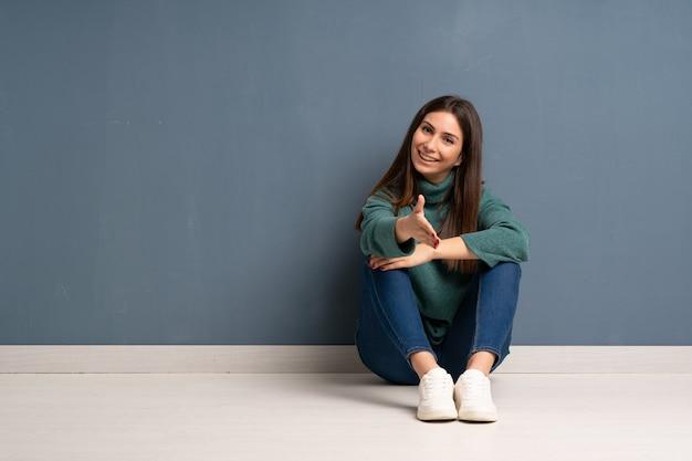 Jonge vrouw zittend op de vloer handen schudden voor het sluiten van een goede deal