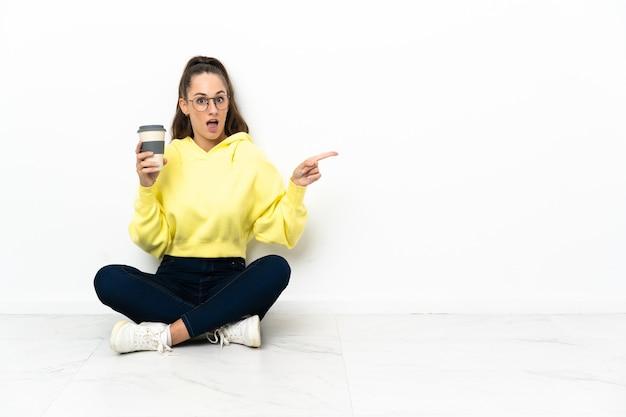 Jonge vrouw zittend op de vloer met een afhaalkoffie verrast en wijzende vinger naar de zijkant