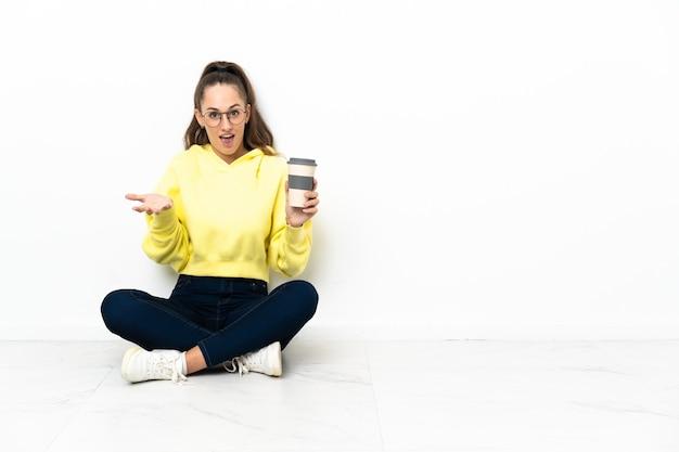 Jonge vrouw zittend op de vloer met een afhaalmaaltijden koffie met geschokte gelaatsuitdrukking