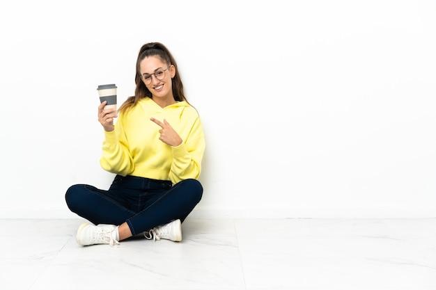 Jonge vrouw zittend op de vloer met een koffie om mee te nemen en erop te wijzen