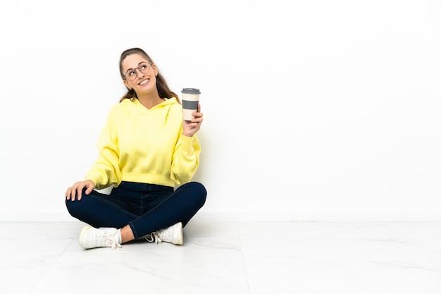 Jonge vrouw zittend op de vloer met een koffie om mee te nemen terwijl ze glimlacht