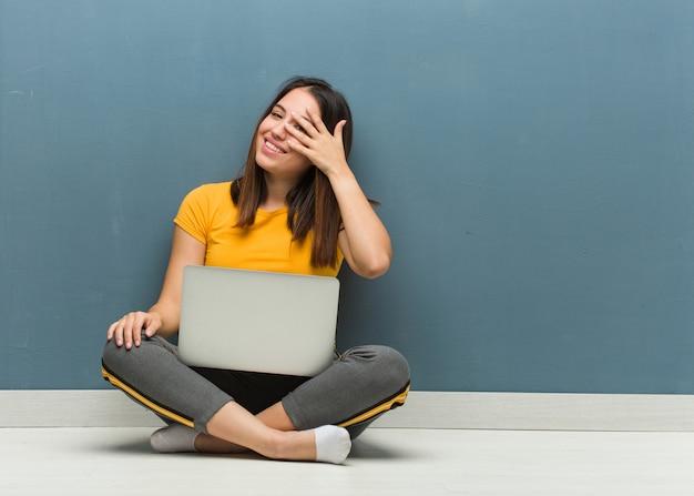 Jonge vrouw zittend op de vloer met een laptop beschaamd en tegelijkertijd lachen