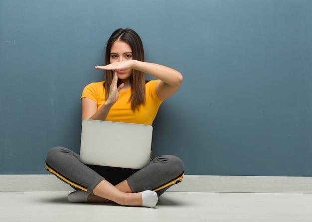 Jonge vrouw zittend op de vloer met een laptop doet een time-out gebaar