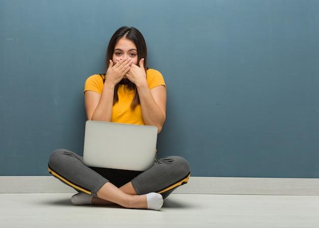 Jonge vrouw zittend op de vloer met een laptop verrast en geschokt