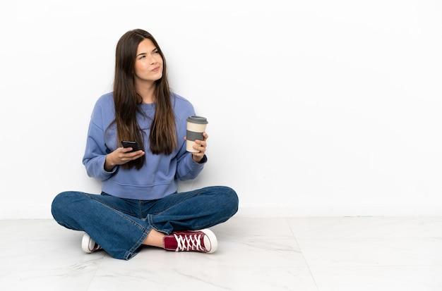 Jonge vrouw zittend op de vloer met koffie om mee te nemen en een mobiel terwijl ze iets denkt