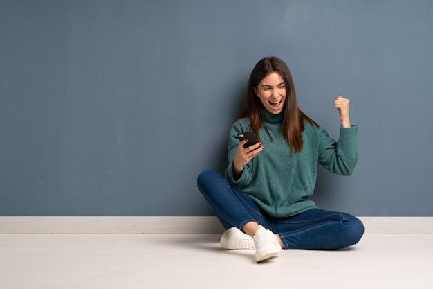 Jonge vrouw zittend op de vloer met telefoon in overwinning positie
