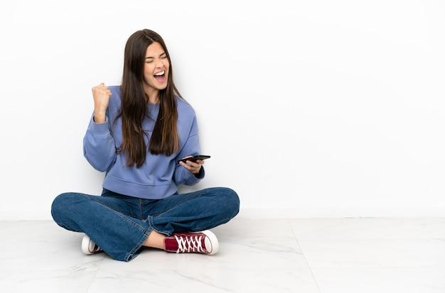 Jonge vrouw zittend op de vloer met telefoon in overwinningspositie