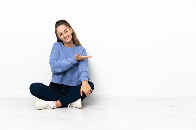 Jonge vrouw zittend op de vloer presenteert een idee terwijl u glimlacht naar