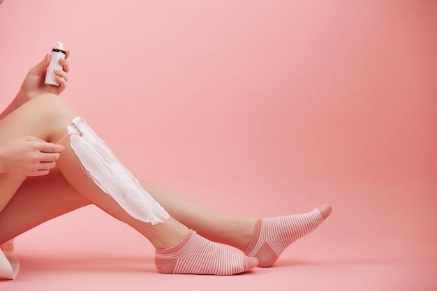 Jonge vrouw zittend op de vloer, room toe te passen en benen scheren