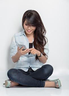 Jonge vrouw zittend op de vloer terwijl ze iets doet met haar smartphone