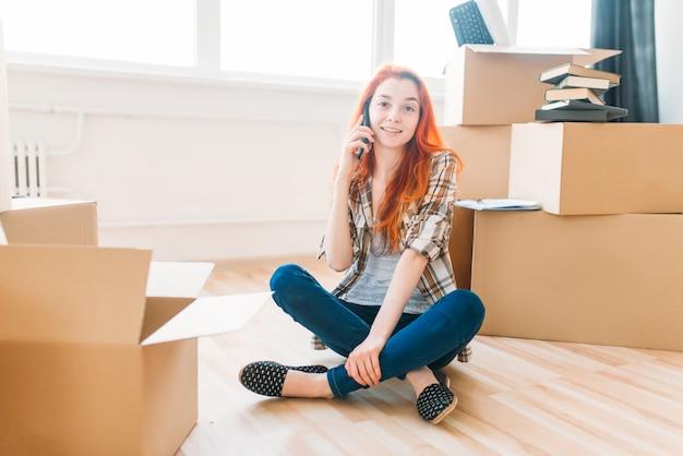 Jonge vrouw zittend op de vloer tussen kartonnen dozen en praten via de mobiele telefoon, inwijdingsfeest. verhuizing naar nieuw huis