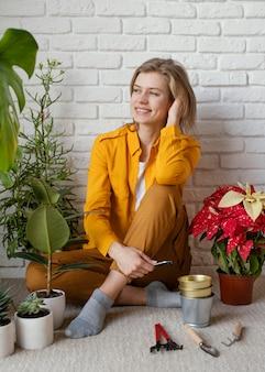 Jonge vrouw zittend op de vloer van haar huis tuin