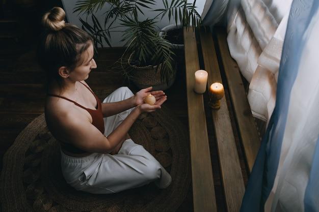 Jonge vrouw zittend op de vloer verlicht kaarsen geniet van meditatie doe yoga oefening thuis mentaal