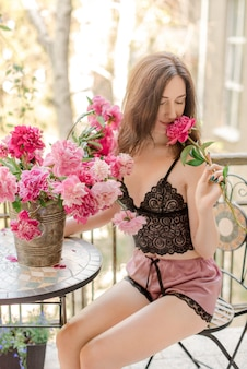 Jonge vrouw zittend op een balkon met bloemen