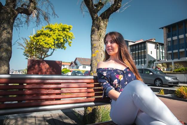 Jonge vrouw zittend op een bankje aan de zeezijde