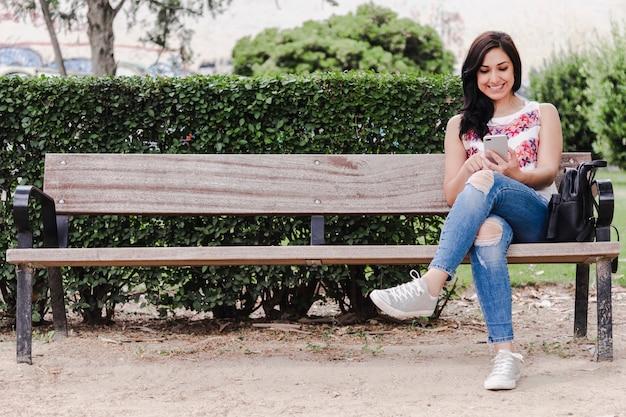 Jonge vrouw zittend op een bankje kijken naar haar mobiele telefoon