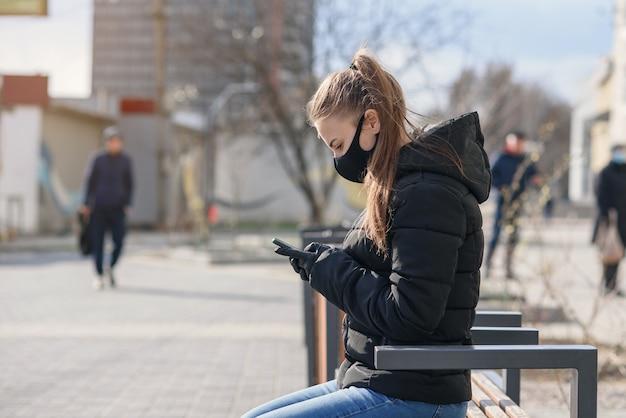 Jonge vrouw zittend op een bankje met medische masker en zwarte kleding