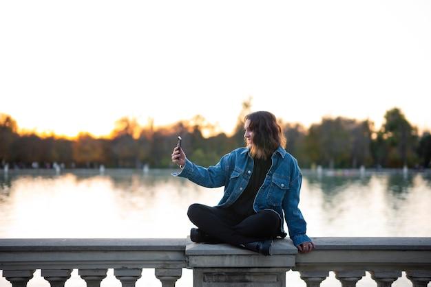 Jonge vrouw zittend op een hek bij een meer