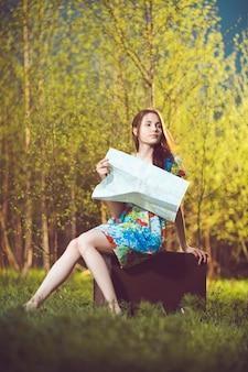 Jonge vrouw zittend op een koffer en het lezen van een kaart in bos
