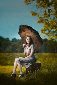 Jonge vrouw zittend op een koffer onder regen en wachten