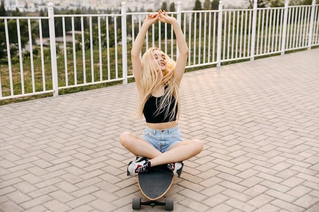Jonge vrouw zittend op een longboard, buitenshuis