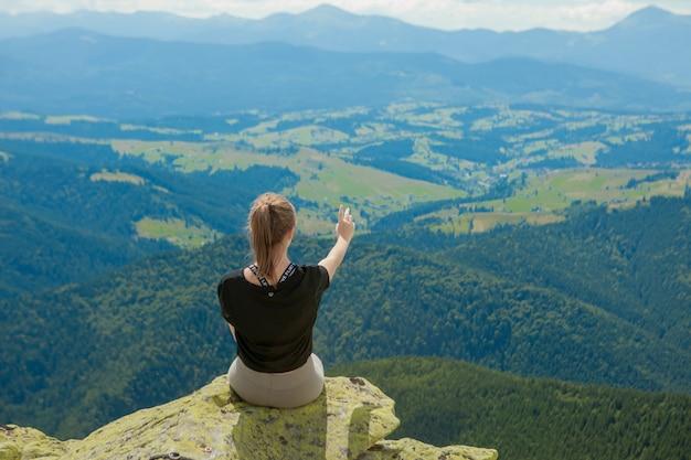 Jonge vrouw zittend op een rots en op zoek naar de horizon.
